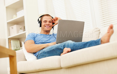 Buy stock photo Happy young guy listening to music on the laptop, relaxing on the couch