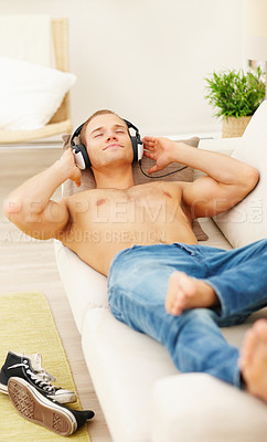 Buy stock photo Smart young man relaxing at home, listening to peaceful music