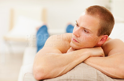 Buy stock photo Young man relaxing on the couch, lost in thought