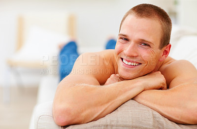 Buy stock photo Portrait of a happy young man relaxing on the couch at home, smiling