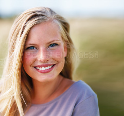 Buy stock photo Portrait of a sweet young blond female smiling while outdoors