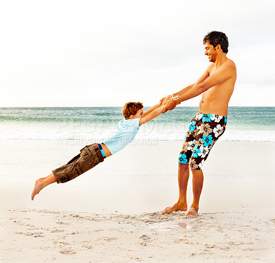 Buy stock photo Full length of a happy man swinging his son at the beach