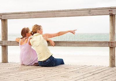 Buy stock photo Rear view of a mother and daughter at the beach sitting by a wooden railing, woman pointing away