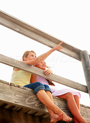 Buy stock photo Upward view of a mother and daughter sitting by a wooden railing, woman pointing away
