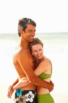 Buy stock photo Happy romantic couple embracing eachother while at the sea shore