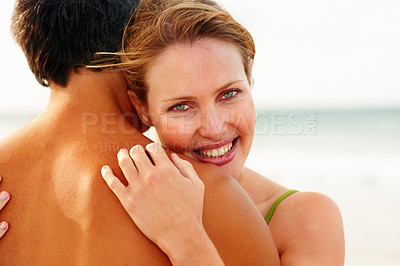 Buy stock photo Portrait of a cute young woman embracing her husband while at the sea shore