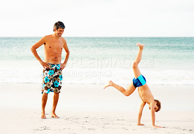 Buy stock photo Full length of a man watching his son doing a cartwheel on the sea shore