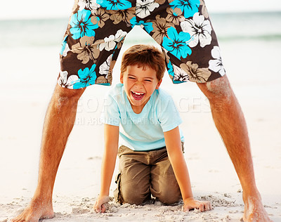 Buy stock photo Portrait of a sweet small boy playing with his father at the sea shore