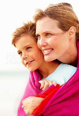 Buy stock photo Cute small boy being embraced by mother while on the beach