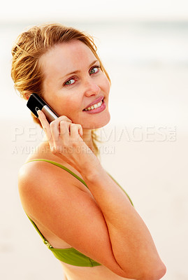 Buy stock photo Pretty young female using a cellphone for communication while at the beach