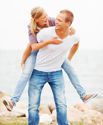 Buy stock photo Happy cute woman being piggy backed by her boyfriend outdoors