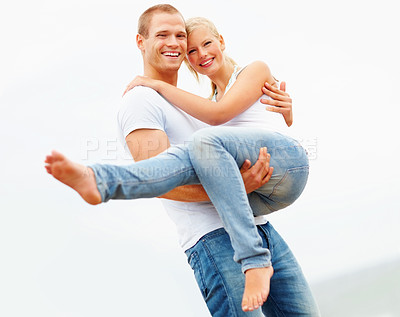 Buy stock photo Handsome guy carrying his girlfriend in his arms, outdoors