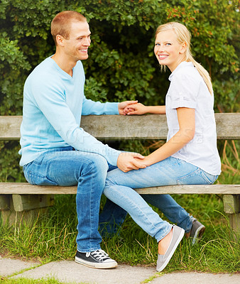 Buy stock photo Happy young couple sitting together on a bench at a park