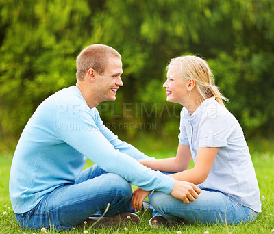 Buy stock photo Cute young couple sitting together on a grass field