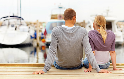 Buy stock photo Rear view of a young couple sitting at the edge of a wooden boardwalk of a harbour
