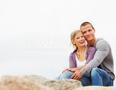 Buy stock photo Portrait of a romantic couple cuddling together on the rocks