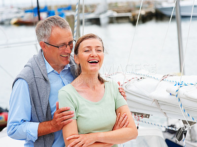 Buy stock photo Happy mature couple laughing while on a sailboat, retirement vacation