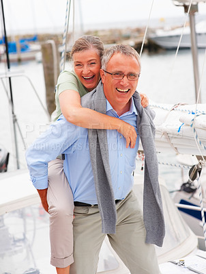 Buy stock photo Happy elderly couple enjoying while in a playful mood on a sailboat