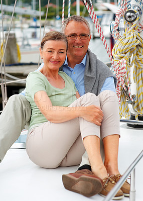 Buy stock photo Portrait of a happy elderly couple sitting on a sailboat
