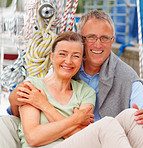 Cute retired couple sitting together on a sailboat
