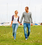 Happy couple walking on a grass field, harbour view at the back