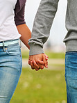 Mid section image of a couple holding hands, outdoors