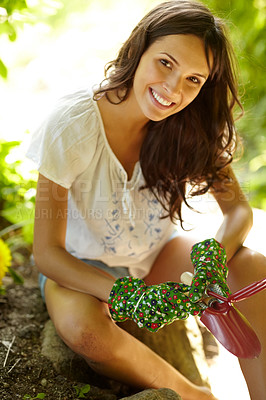 Buy stock photo Closeup portrait ofan attractive young woman holding gardening tools and siiting outdoor in a garden