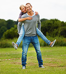 Happy young man piggybacking his girlfriend, at the park