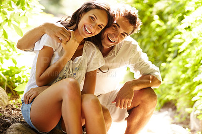 Buy stock photo Romantic young couple sitting together in forest and smiling