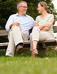 Happy old couple sitting on a bench at the park