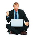 Excited young business man working on the laptop while sitting on the floor