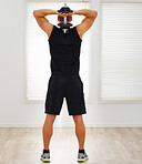 Rear view full length of a young guy exercising his triceps with a dumbbell