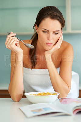 Buy stock photo Pretty woman eating breakfast and reading a magazi