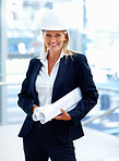 Portrait of a female architect wearing a hardhat, holding blueprints