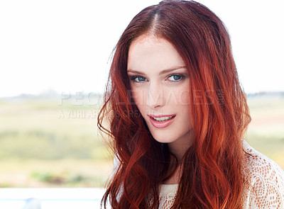 Buy stock photo A beautiful young redhead woman standing outside looking at the camera