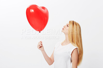 Buy stock photo A gorgeous young blonde woman holding a heart while isolated on a white background