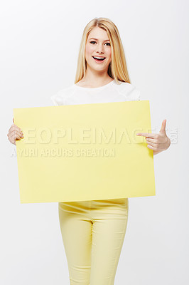 Buy stock photo A pretty young blonde woman holding a blank placard up for your copyspace