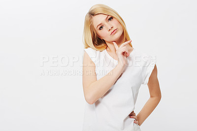 Buy stock photo A pretty young blonde woman looking undecided while isolated on a white background
