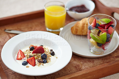 Buy stock photo Closeup of a breakfast tray with juice, fruits salad, a croissant and muesli