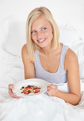 Buy stock photo An attractive young woman eating her breakfast in bed