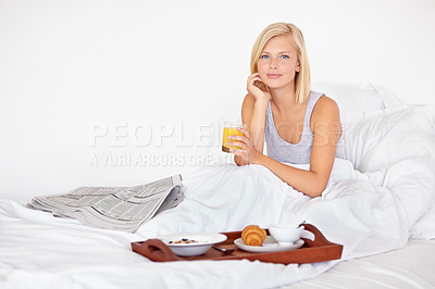 Buy stock photo A pretty young woman getting the day off to a great start with breakfast in bed