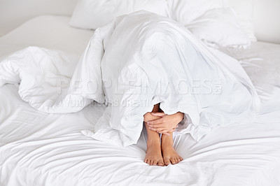 Buy stock photo A depressed young woman trying to escape the day by hiding under the covers