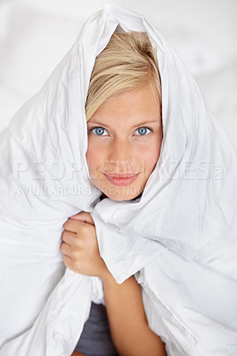 Buy stock photo Shot of an attractive young woman poking her head out from her duvet and smiling at the camera