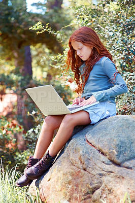 Buy stock photo A young girl working on her laptop while sitting on a rock outside
