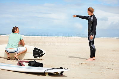 Buy stock photo A surfer pointing towards the ocean while his friend sits holding a surfboard