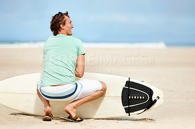 Buy stock photo A young surfer crouched on the beach and looking away at the waves