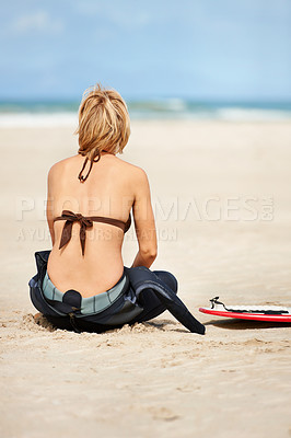 Buy stock photo Rear view of a young female surfer looking away on the beach