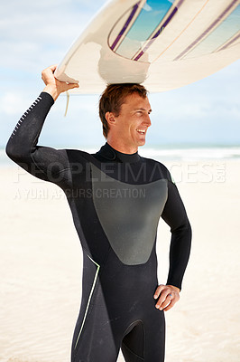 Buy stock photo Shot of a young male surfer at the beach carrying his board on his head