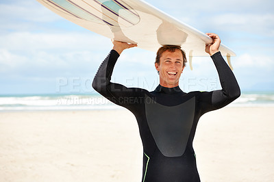 Buy stock photo Shot of an excited young surfer at the beach carrying his board on his head