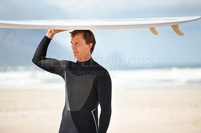 Buy stock photo Shot of a young male surfer carrying his board on his head
